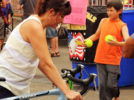 Christina Caro of Mammoth Lakes, Calif., rides a bicycle while shopping for one at the Reno Bike Project Saturday during the Positively Fourth Street block party.