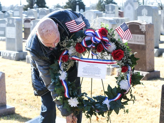 Florist Coby Palmer, of Colby Palmer Designs, delivers a memorial wreath to the grave of Milton Olshewitz at Beth-El Cemetery in Indianapolis on Wednesday, Dec. 28, 2016.