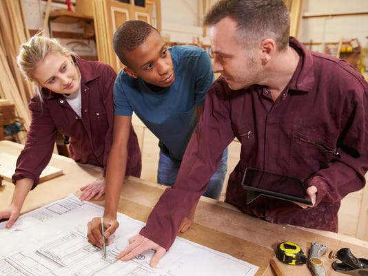 Carpenter With Apprentices Looking At Plans In Workshop