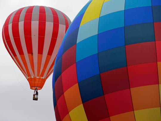 Pilots and crews get hot-air balloons off the ground during Burger Fest Saturday in Seymour.
