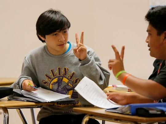 Jose Anzaldo goes through an exercise with a classmate