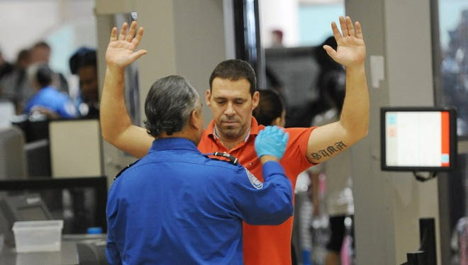 An air traveler is patted down after passing through a full-body scanner at the Transportation Security Administration checkpoint at  Los Angeles International Airport on Feb. 20.