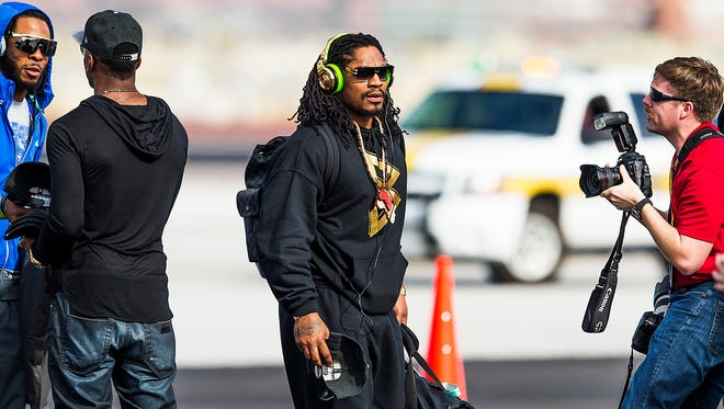 Seattle Seahawks' Marshawn Lynch deplanes after arriving at Sky Harbor International Airport on Jan. 25, 2015.  They will play in Super Bowl XLIX against the New England Patriots.