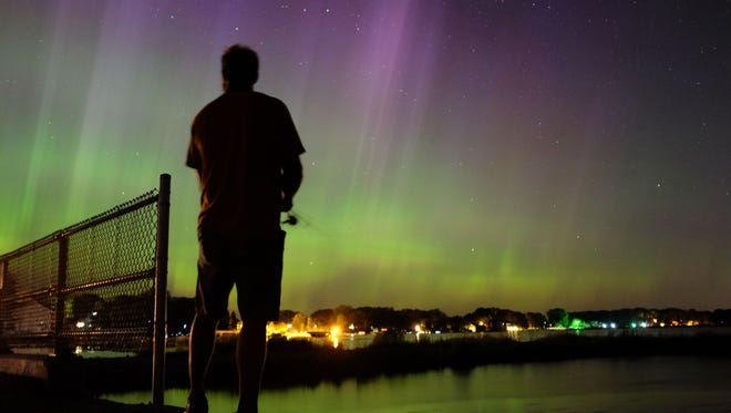 Wade Kitner looks at the northern lights as he fishes in Ventura, Iowa, on June 23, 2015.