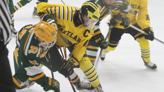 Hartland's Jake Behnke takes a faceoff against Midland Dow's Austin Ieuter during the Eagles' 6-1 victory in the state hockey quarterfinals on Tuesday, March 6, 2018.