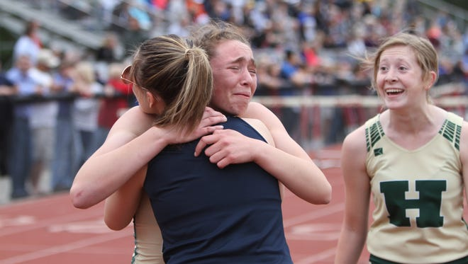 Howell's Emily Endebrock (left, facing camera) is overcome with emotion after breaking the 42-year-old school record in the 400 meters in the regional track and field meet on Friday, May 18, 2018. Teammate Ashlyn Tait (right) shares in the excitement.