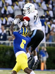 Delaware State's Keyjuan Selby intercepts a pass in front of Delaware's Jamie Jarmon in the first quarter at Delaware Stadium.