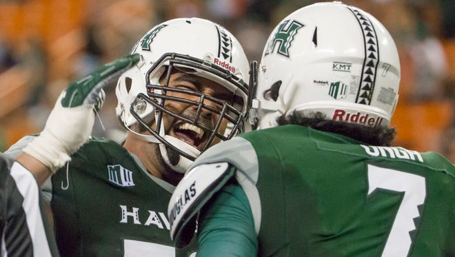 Hawaii offensive lineman Leo Koloamatangi, left, congratulates teammate Metulsela Unga after Unga scored a touchdown against Nevada.