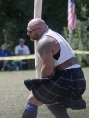In the professional athlete division, Andy Vincent tosses the caber.