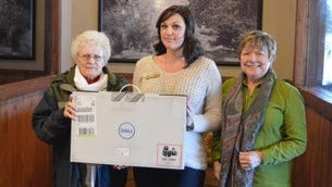 Formalizing the laptop donations are from left, Kiwanis Club member Carolyn Durrett, Kiwanis Club president Ashley Dalton and Rev. Laurie Benavides, president of High Mountain Youth Project.