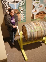 """Collections Manager Lizz Ricci turns a composting tumbler, part of the """"Green Revolution"""" exhibition opening today at the Farmington Museum at Gateway Park."""