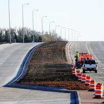 A construction places cones along the median on Highway 11 between 26th Street and 57th Street in Sioux Falls on Friday, Oct. 25, 2013. (Joe Ahlquist / Argus Leader)