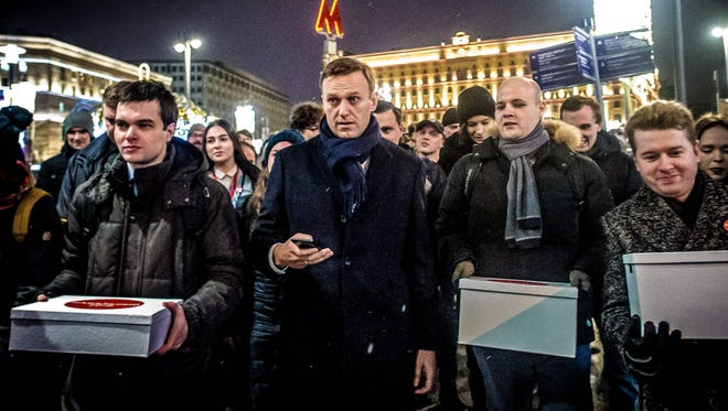 Supporters of Russian opposition leader Alexey Navalny, center, carry boxes with signatures to nominate him as opposition candidate for the forthcoming presidential election in Moscow on Dec. 24, 2017.