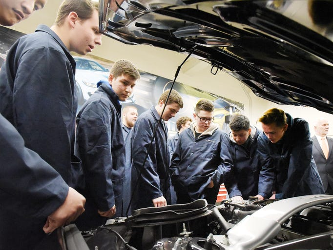 Students look over the 5.2 Liter engine in a Cobra