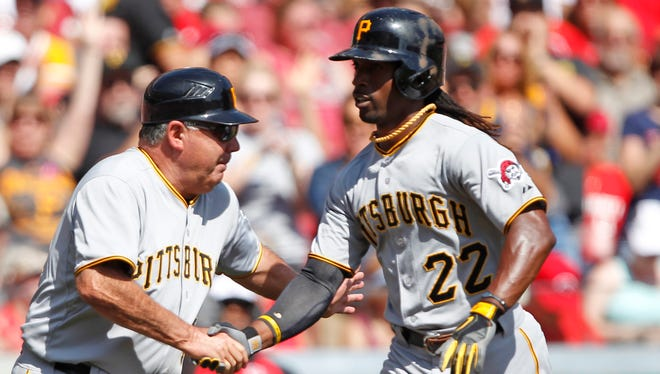 Pittsburgh's Andrew McCutchen is congratulated by third base coach Nick Leyva after hitting a home run during the Pirates' win Saturday over the Reds.