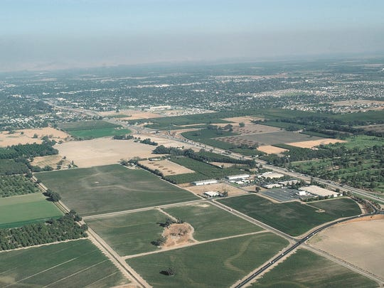 An aerial file photo of Visalia looking southeast over Plaza Drive and Highway 198 shows the layer of smog that hovers over the Valley.