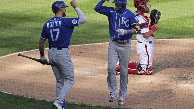 Kansas City Royals' Whit Merrifield, center, celebrates with Hunter Dozier after hitting a solo home run during the eighth inning.