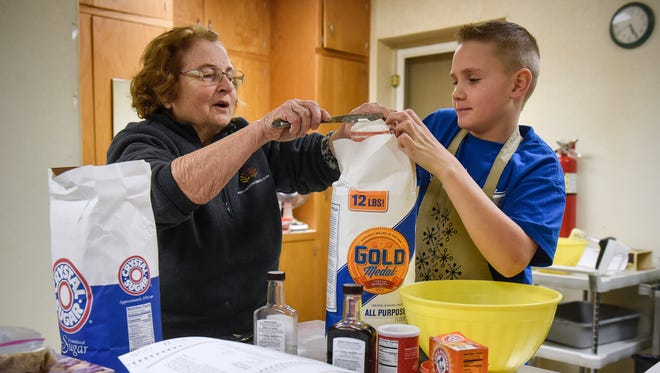 Sally Borgert helps Carl Shobe measure flour while preparing a batch of Swedish rusks Wednesday, Dec. 13, while baking for the upcoming Santa Lucia Festival of Lights at Salem Lutheran Church in St. Cloud.
