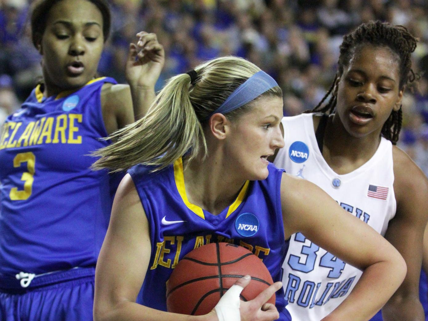Delaware guard Lauren Carra pulls in a first half rebound in front of teammate Jaquetta May (left) and North Carolina's Xylina McDaniel.
