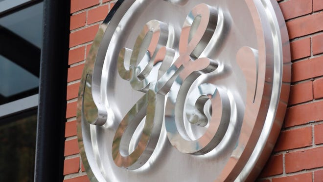 File poto taken in 2017 shows the General Electric logo on the wall of the  company's interim offices in Boston