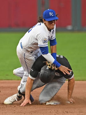 Kansas City Royals second baseman Nicky Lopez (1) tumbles over Chicago White Sox base runner Adam Engel (15) after turning a double play in the fifth inning Saturday at Kauffman Stadium.