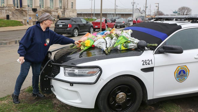 Paula Feltner of Des Moines lays a bouquet of yellow tulips on the hood of a Des Moines police squad car in memory of two police officers killed early Saturday morning in a car accident on Interstate 80 in Waukee.