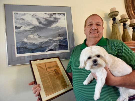 Russ Humphrey poses with a picture of the S.S. Carl D. Bradley and his dog Friday, April 14, at his home in Chesterfield Township.