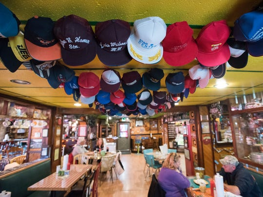 Trucker hats decorate the ceiling Sunday, April 23, at Foxfire Fixin's in Marine City.