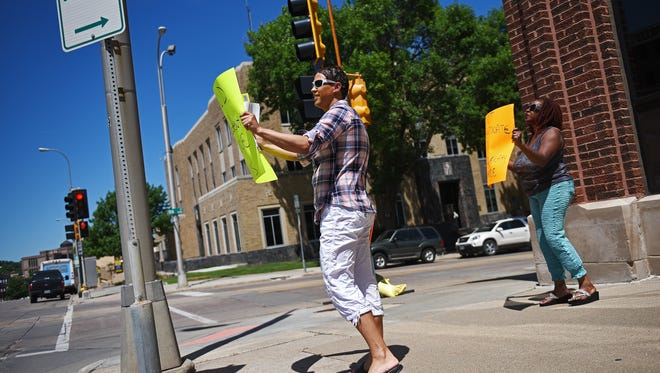 Sierra Broussard, left, and a another demonstrator that wanted to remain anonymous stand at the corner of 9th Street and South Dakota Avenue holding signs during a demonstration to pressure city officials into bringing transgender people under the umbrella of protective classes in Sioux Falls Friday, July 8, 2016, in downtown Sioux Falls.