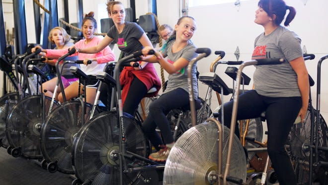 Members of Iron Girls warm up on stationary bicycles before their work out at CrossFit Asheville October 12, 2016.