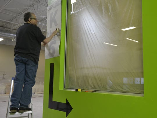 Church volunteer Ken Merrell of Green Bay affixes lettering to a wall in a newly designed hallway that leads to the children's area off the front gathering space at the new Life Church in De Pere on Tuesday, May 17, 2016. Life Church will hold its first Sunday morning services in the former Sportsman's Warehouse retail store at 1551 Lawrence Drive on June 12.