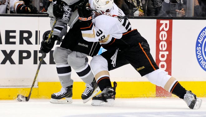 Los Angeles Kings right wing Dustin Brown (23) moves the puck defended by Anaheim Ducks left wing Matt Beleskey (39) during the second period at Staples Center.