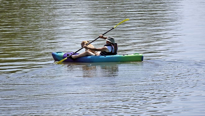 A man kayaks on Charles Mill Lake with his dog as a passenger Monday.