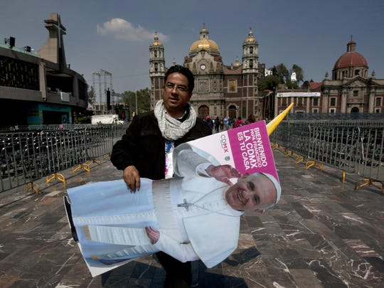 A worker carries a life-size cutout of Pope Francis