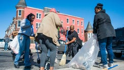 Volunteers clean up trash and shattered glass in front