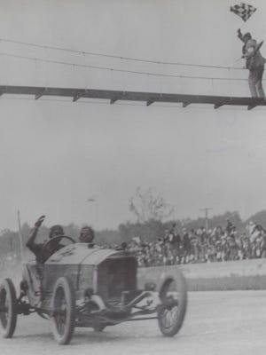 Ralph DePalma waves as he takes the checkered flag in the 1915 Indianapolis 500.  Note the flagman on the overhead foot-bridge.