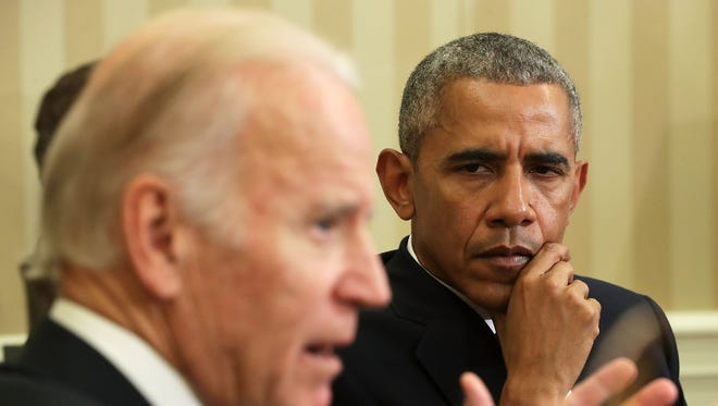 Vice President Biden speaks as President Barack Obama listens during a meeting to release the Cancer Moonshot Report in the Oval Office of the White House Oct. 17.