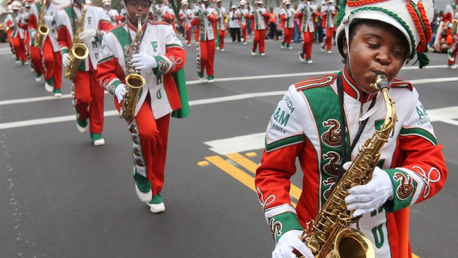 FAMU Marching 100 saxophonists march up West Tennessee Street during last year's Homecoming Parade.