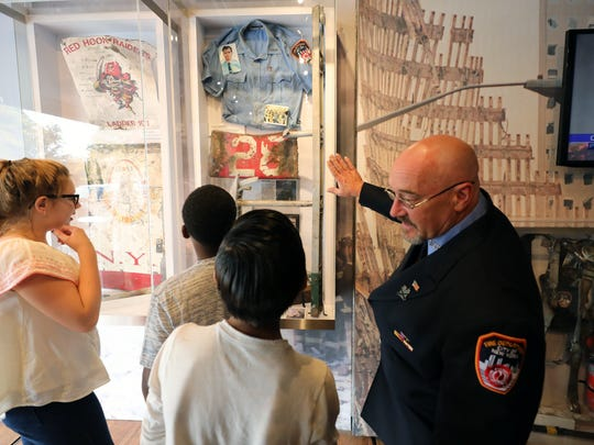 Retired New York City Firefighter Doug Guercia talks to students inside a traveling museum operated by the Stephen Siller Tunnel to Towers Foundation as it visits Albert Leonard Middle School in New Rochelle on Wednesday to educate students about Sept. 11, 2001.