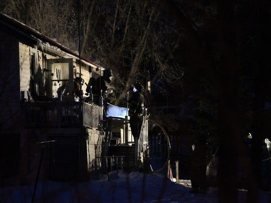 Firefighters work at the back of a residence in Mosinee. Two were injured in the fire, Thursday, February 12, 2015.