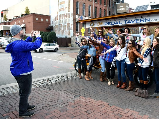 Nashville Pedal Tavern driver Todd Griggs takes a group photo for a bachelorette party that he drove to local bars in downtown Nashville on Sat.  Nov. 7, 2015.