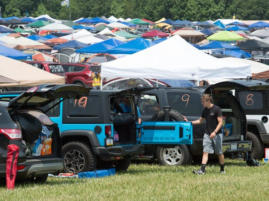 Austin Jer-Don of Villanova, Pa., removes items from a Jeep to set up camp at the Firefly Music Festival in Dover.