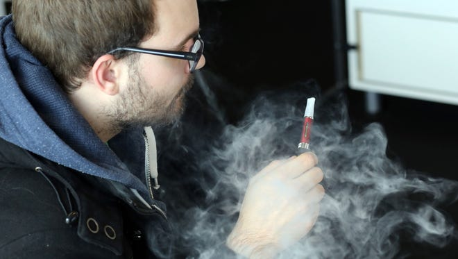 A man smokes an e-cigarette as he visits Vapexpo, an international exhibition to promote e-cigarette, in Bordeaux, western France, on March 13, 2014. E-cigarettes are battery-powered gadgets that deliver nicotine through a vapor that may be fruit or candy-flavored.