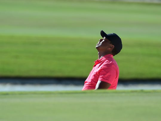 Tiger Woods reacts after a shot from a bunker on 17 during the final round of the Hero World Challenge golf tournament at Albany Golf Club in Nassau, Bahamas, Sunday, Dec. 3, 2017. (AP Photo/Dante Carrer)