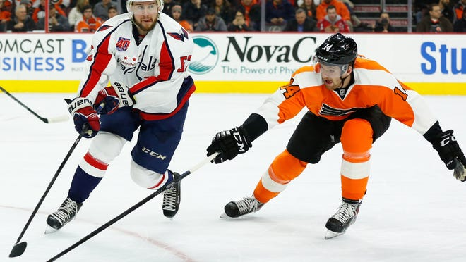 Washington Capitals defenseman Mike Green (52) skates with the puck against the checking of Philadelphia Flyers center Sean Couturier (14) during the first period at Wells Fargo Center on Thursday. The Flyers defeated the Capitals 3-2 in overtime.