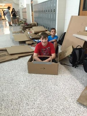 Hunter Hollywood (front) and Francis Kinsella are participating in Delsea Regional Middle School's SHAPE program, where children are building boats out of cardboard.