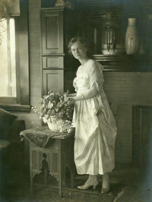 Elisabeth Ball arranging flowers in her family home, Oakhurst, around 1915.