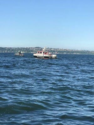 A Seattle Fire Department boat crew searches for a 70-year-old man who went missing after his plane crashed in the water off Bainbridge Island on Sunday. The aircraft was reported as a 1974 two-seater fixed-wing single-engine.    U.S. Coast Guard photo by Petty Officer 3rd Class Dustin Lay.