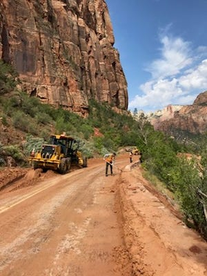 Crews work to remove mud and other debris from the Zion-Mount Carmel Highway in Zion National Park on July 12, 2018.