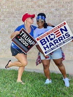 Cedar Park neighbors Marne Litton, left, and Tasha Hancock pose with their campaign signs to show that people with opposing political views can be friends.
